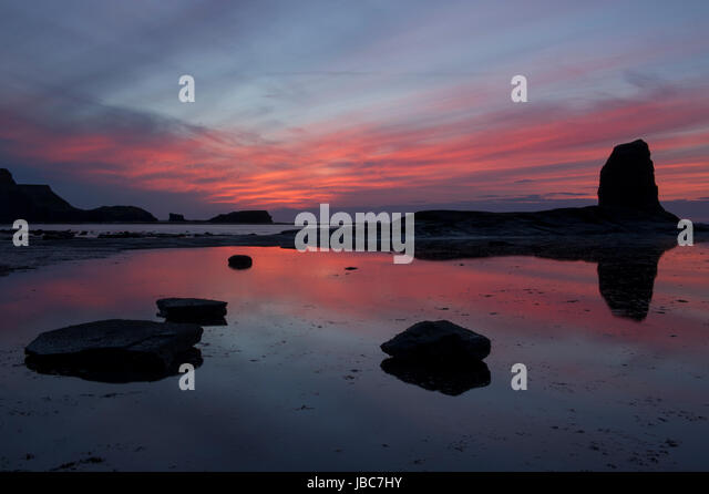 A beautiful orange sunset over Saltwick Bay, Whitby on the North Yorkshire Coast - Stock Image