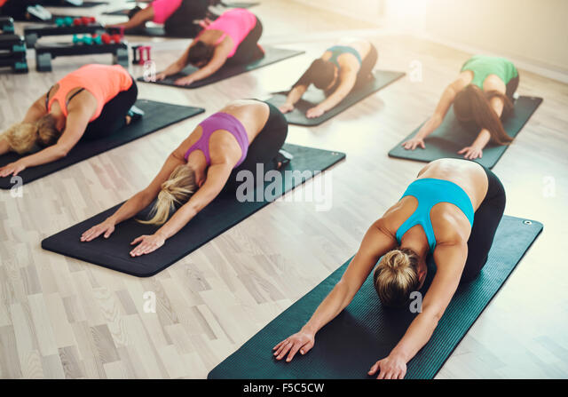 fitness, sport, training, yoga and people concept - smiling woman doing exercise in gym - Stock Image