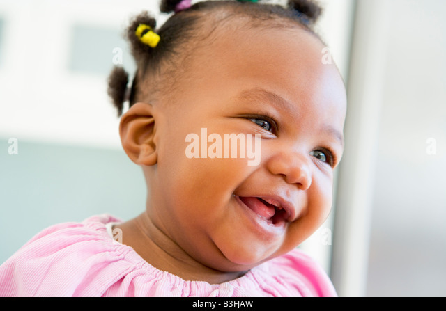 Baby indoors laughing - Stock Image