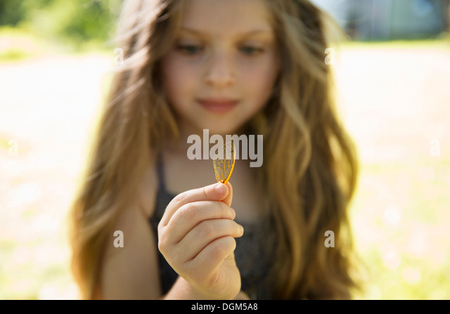 A young girl with long blonde, holding a delicate lacey patterned discarded butterfly wing. - Stock Image