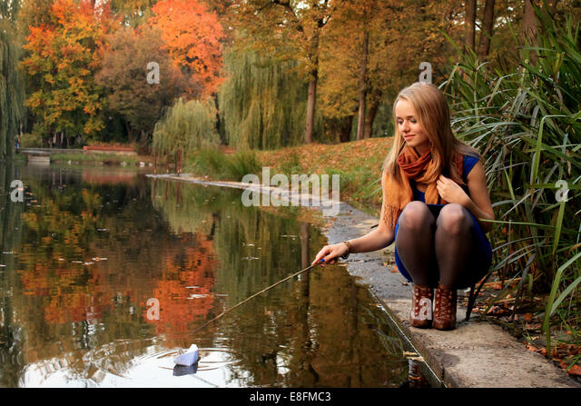 Young woman playing with paper ship on pond - Stock-Bilder