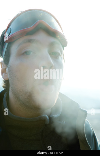 Young man breathing out into cold air - Stock Image