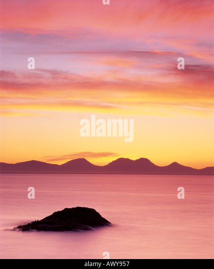 The Paps of Jura seen from the Kintyre Peninsular at sunset, Argyll and Bute, Scotland, UK - Stock Image