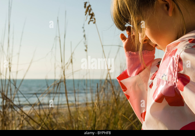 Young girl outdoors, sea in background - Stock Image