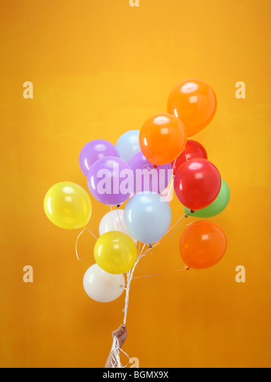 colorful balloons in a bunch held by a hand with orange background - Stock Image
