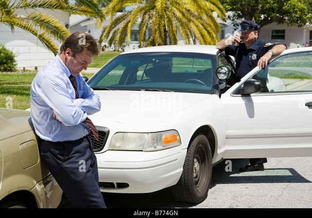 Embarassed looking businessman pulled over by the police Focus is on the businessman - Stock Image