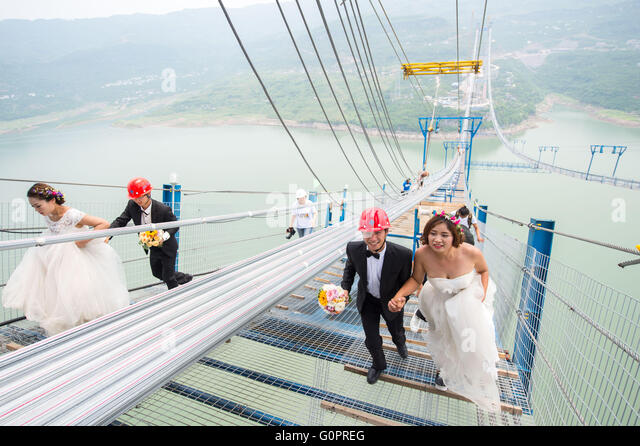 Chongqing. 4th May, 2016. Young couples walk up to have their wedding photos taken on a suspension bridge over the - Stock Image