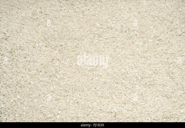 Textured background of rice grains on the surface - Stock Image