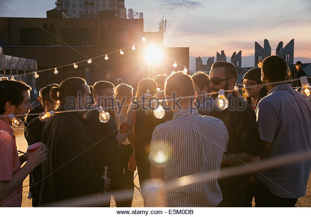 String lights over crowd at rooftop party - Stock Image