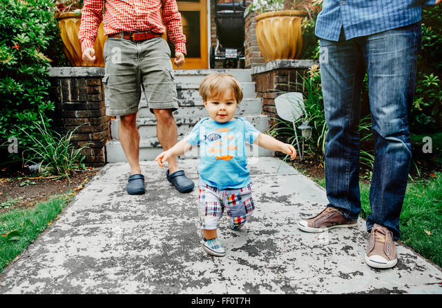 Gay fathers and baby son standing outdoors - Stock Image