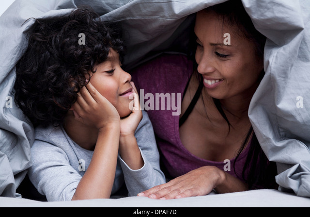 Mother and son hiding underneath the duvet - Stock Image