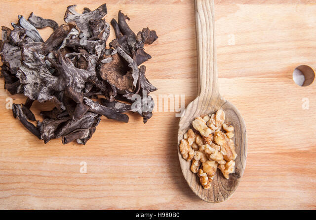 Horn of Plenty mushrooms on light wooden chopping board with wooden spoon full of walnut - Stock Image