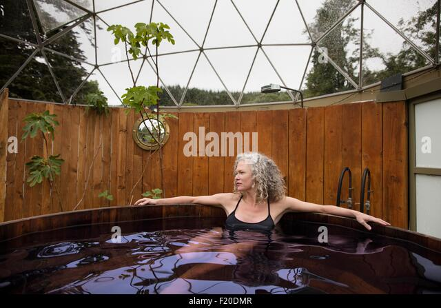 Mature woman relaxing in hot tub at eco retreat - Stock Image