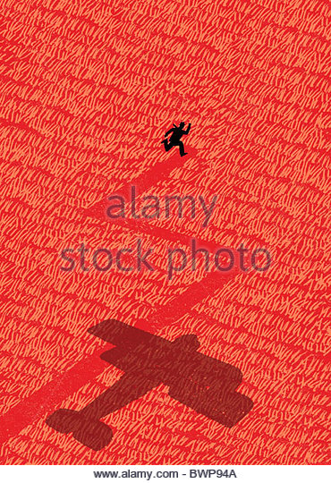 Old-fashioned airplane chasing man through field - Stock Image