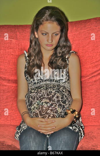 Pregnant teenager looking away from camera - Stock-Bilder
