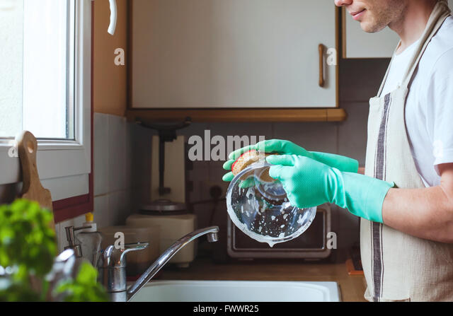 man washing dishes in the kitchen sink at home, close up of hands with sponge and soap, housework - Stock Image