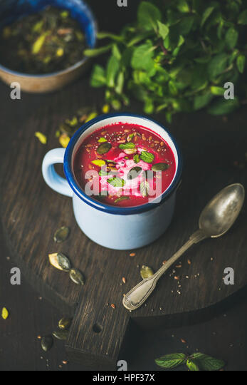 Spring detox beetroot soup with mint, pistachio, chia, flax, pumpkin seeds in blue enamel mug over dark wooden background. - Stock Image