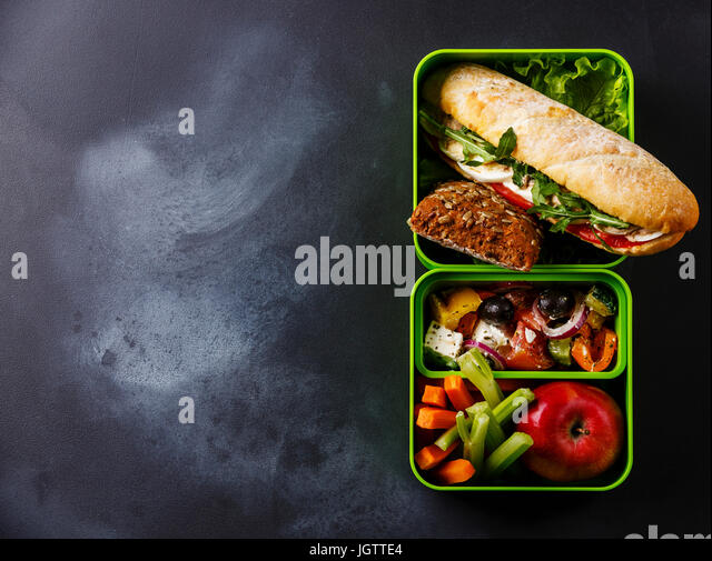 Take out food Lunch box with Tuna and egg Sandwich, Greek salad and vegetables on blackboard background copy space - Stock Image