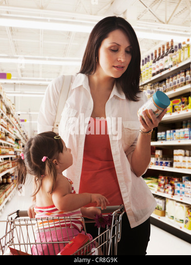 Mother reading label on baby food jar in supermarket - Stock Image