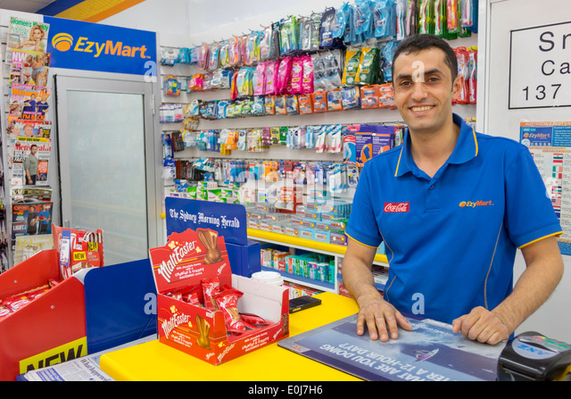 Australia NSW New South Wales Sydney CBD Central Business District EzyMart convenience store inside counter man - Stock Image