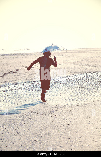 Girl running on beach with umbrella - Stock Image