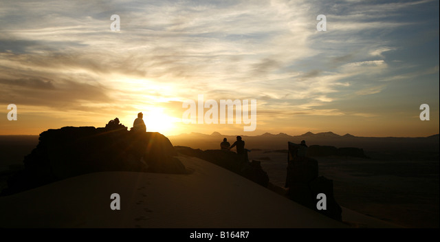 Couple looking at sunset at Tagelment Samedat Tassili Ahaggar Sahara desert Algeria - Stock Image