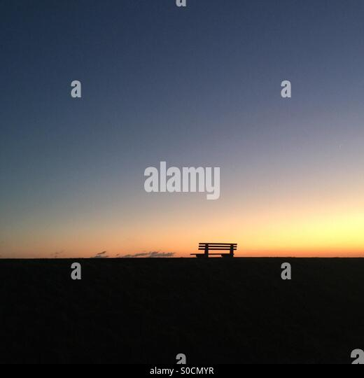 Lone bench in the sunset - Stock Image