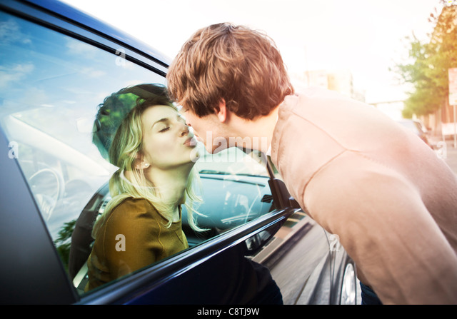 USA, Washington, Seattle, Young couple kissing through window of car - Stock Image