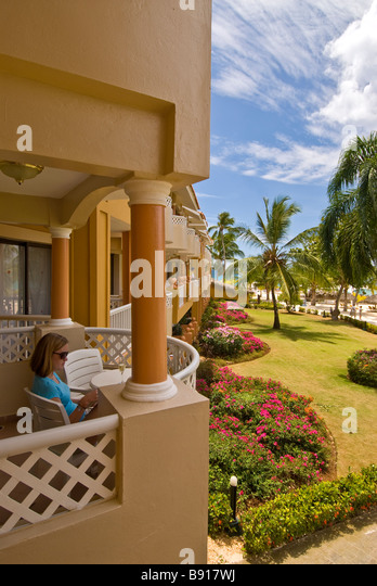 Woman sitting on hotel balcony Bayahibe Viva Wyndham Dominicus Palace all-inclusive resort with palm trees Dominican - Stock Image
