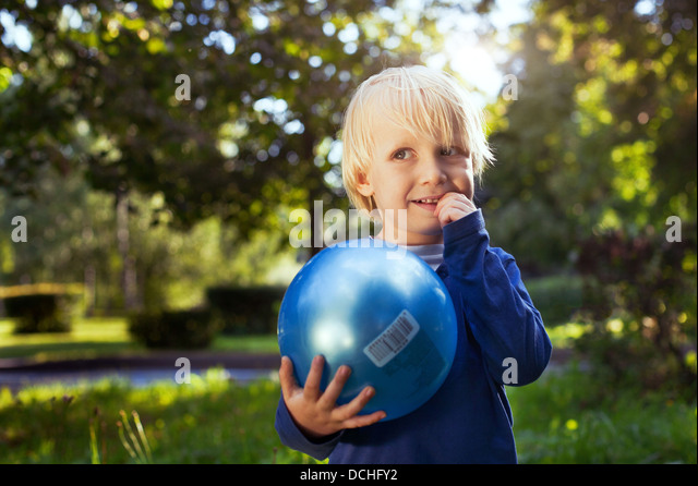 little cute boy with the ball looking up - Stock Image