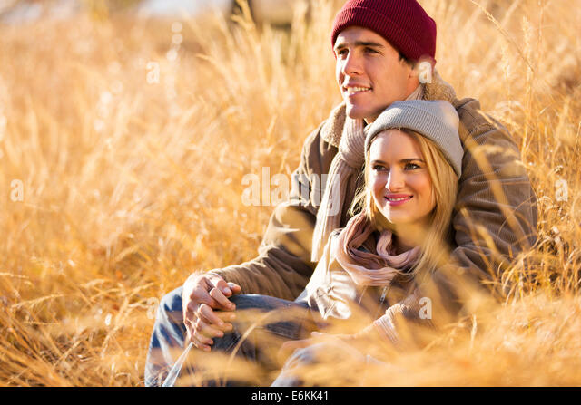 romantic young couple sitting outdoors in fall - Stock Image