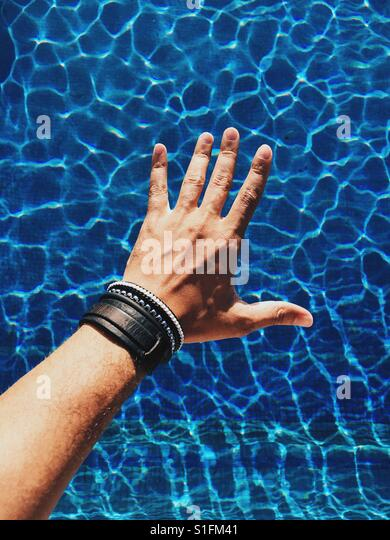 A male hand wearing bracelets outstretched over a blue swimming pool during the warm Caribbean summer. Beautiful - Stock-Bilder