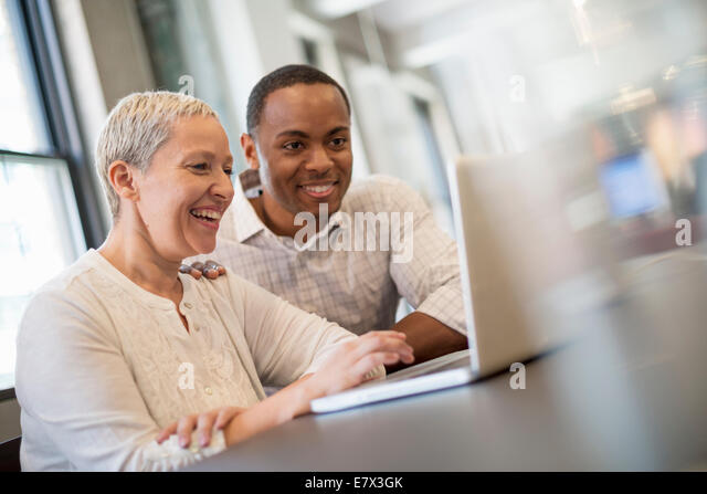 Office life. Two people, a man and woman looking at a laptop screen and laughing. - Stock Image