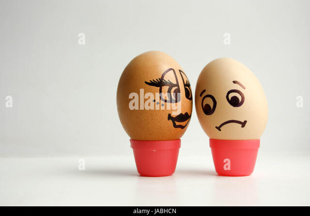 Eggs with painted face. The concept of love between white and black is unrequited. Photo for your design. - Stock Image