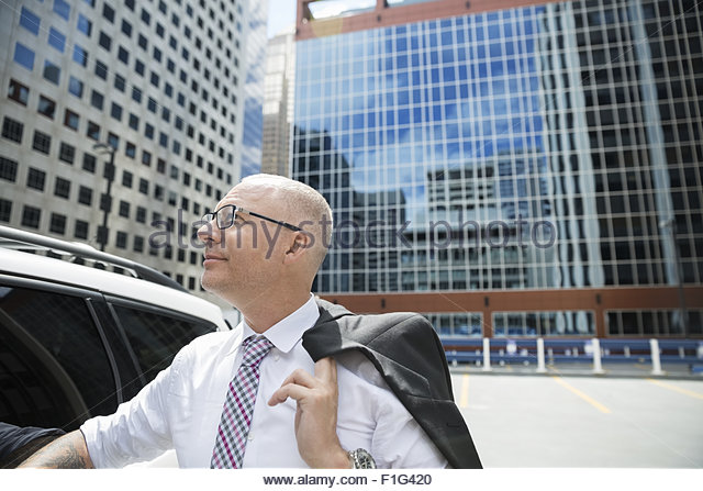Businessman looking up at highrises in city - Stock Image