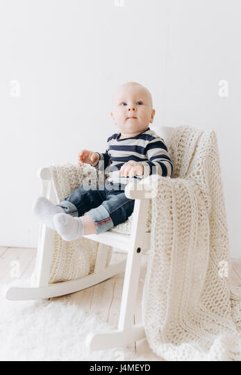 Curious Caucasian baby boy sitting in chair - Stock-Bilder