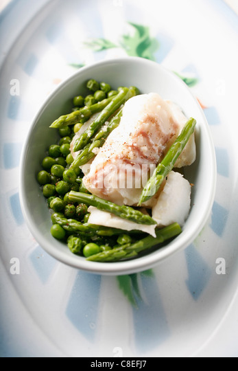 Steam-cooked cod with peas and green asparagus - Stock Image