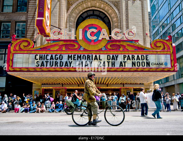 A veteran in WWII uniform rides a bicycle past the Chicago Theatre during a Memorial Day Parade down State Street - Stock Image