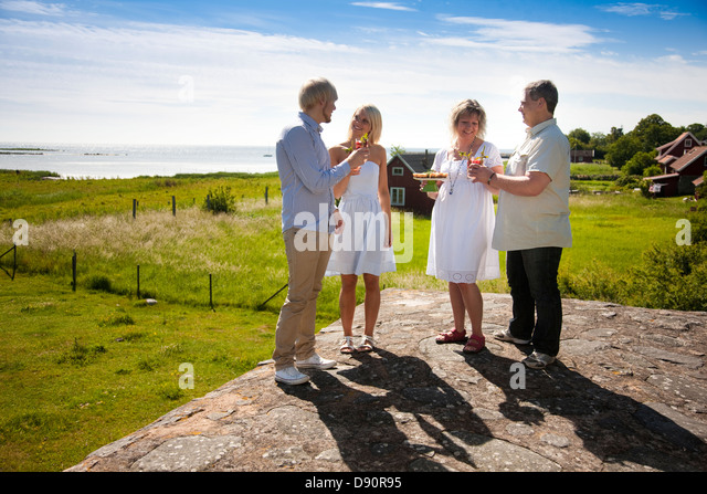 Couples having food and drink at coast, smiling - Stock Image