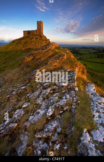 Late evening sunlight illuminates the old hilltop church of Brentor on the edge of Dartmoor. - Stock Image