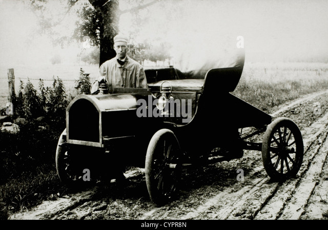 Man Standing Near Automobile on Dirt Road, USA, 1908 - Stock Image