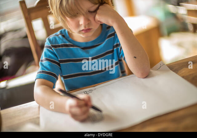 Seven year old boy drawing at the table. - Stock-Bilder