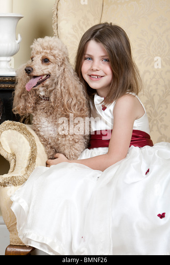 Shot of a Happy Blonde Girl in Large Armchair with an Apricot French Miniature Poodle - Stock-Bilder
