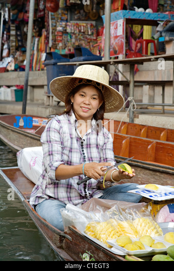Selling food and souvenirs at the Damnoen Saduak floating market located about 62 miles outside of Bangkok Thailand - Stock-Bilder