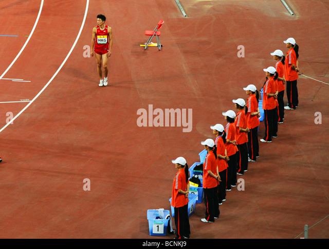 An athelete from Hong Kong walks pass a row of janitors, Beijing, China - Stock Image
