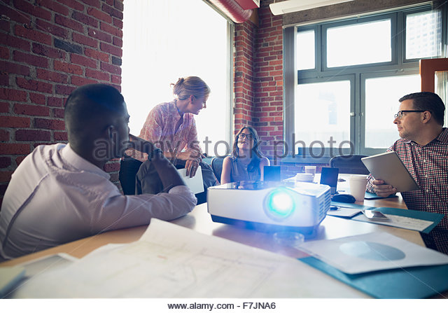 Business people meeting in conference room with projector - Stock Image