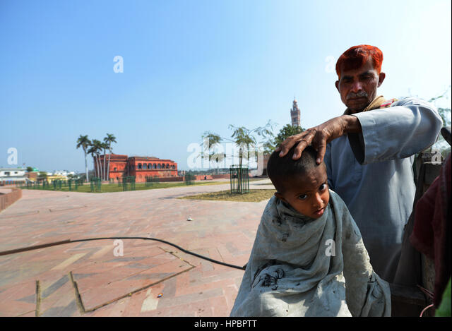 A small boy getting a haircut on Husanabad road near the old clock tower in Lucknow. - Stock Image