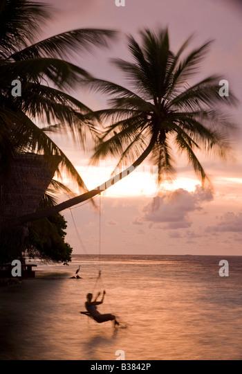 Girl swinging on rope swing at sunset on South Ari Atoll in Maldives near India - Stock-Bilder
