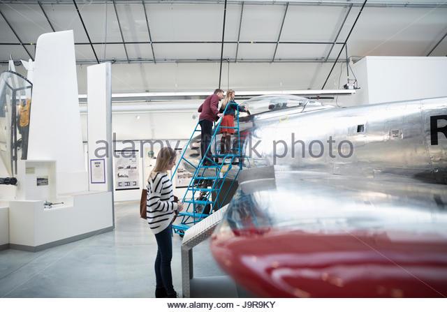 Family looking at airplane in war museum hangar - Stock-Bilder