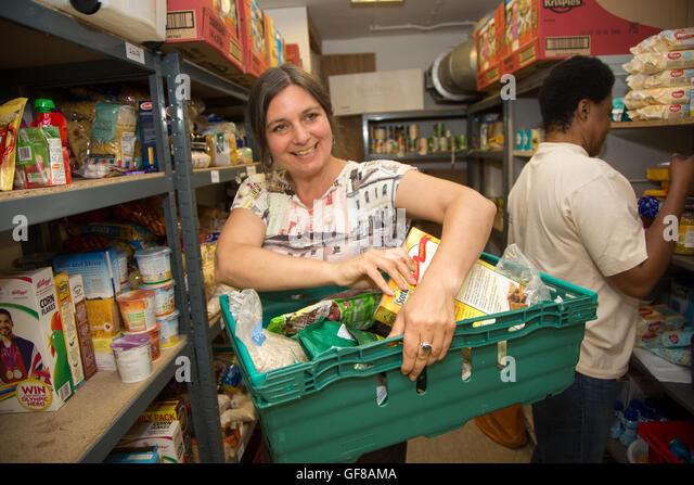 Volunteers stock a foodbank with provisions. - Stock Image